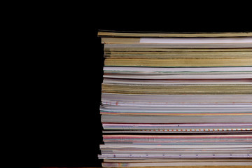 Pile of  journals in front of  black background.