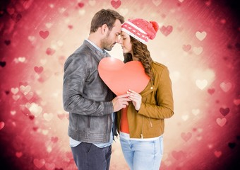 Composite image of couple holding a heart