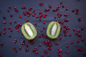 Fresh kiwi halves on a black background