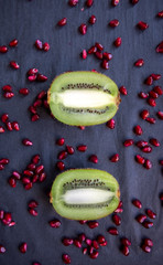 Two parallel halves kiwi and pomegranate seeds on black backgrou