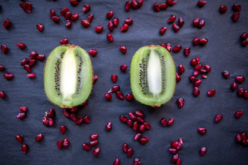 Two halves of kiwi on black background with red pomegranate seed