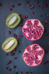 Two halves of pomegranate and kiwi on black background