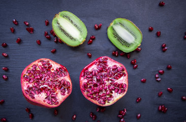 Half pomegranate with seeds and kiwi on black background