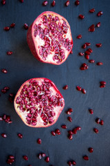 Half pomegranate and seeds on black background