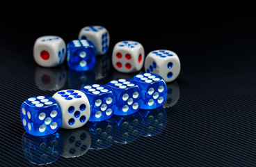 blue and white dices on the glossy black background