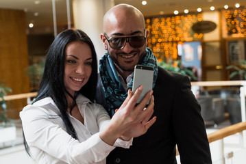 Arab businessman and girl making selfie in the shopping center