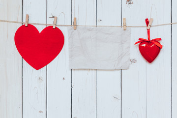 Red heart and old paper blank hanging at clothesline on wood whi