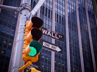 View on Wall street yellow traffic light with black and white Wall street, One way pointer guides. Green traffic light one way to New York NYC Wall street banks money dollars finance offices