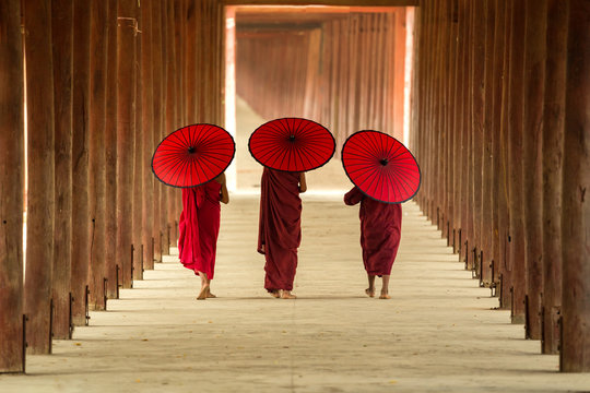 Tree novice monks walking in the pagoda temple,Mandalay,Myanmar.