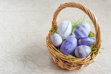 Easter wicker basket with colored eggs on white board.
