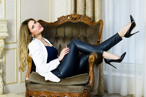 fd92d84b7 Blonde Girl in leather pants sitting in a couch. Luxury interior scene.  Studio shot