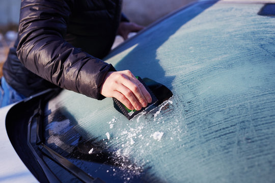 Man scraping ice from the windshield
