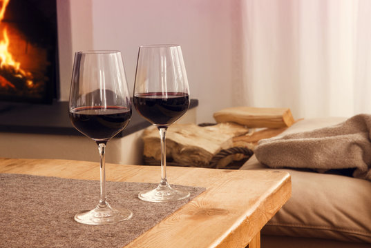 glasses of red wine in front of fireplace