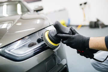 Car detailing - Hands with orbital polisher in auto repair shop.