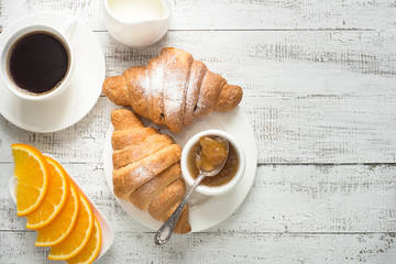 Croissant jam coffee orange juice at white wooden table. Top view with copy space