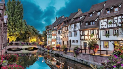 Fototapete - Colorful traditional french houses on the side of river in the evening in Colmar, France (static image with animated sky and water)