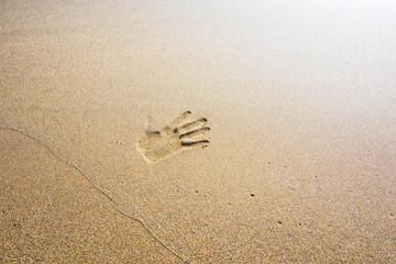 Handprint on beach sand