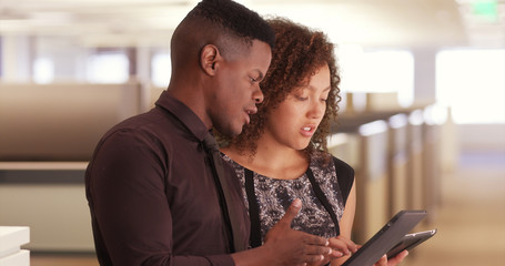 Two black office workers using pads in a modern workplace