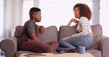African American man and woman talk while relaxing on their couch in their living room