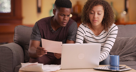 African American couple pays their bills on their laptop
