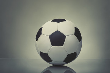 soccer ball with reflection on a table on a gray background