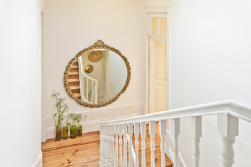 Beautiful Staircase With a Mirror Frame and Hardwood Floor
