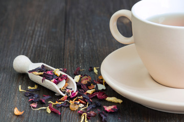 A cup of tea and a wooden spoon with dried tea leaves