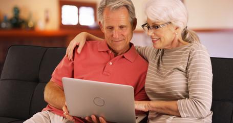 Closeup of senior couple using laptop at home