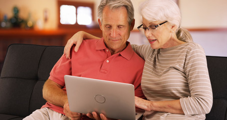 Closeup of older couple using laptop at home