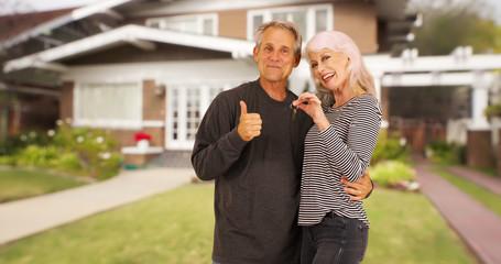 Happy new senior homeowners smiling at camera