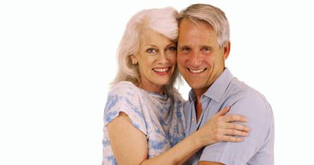 Smiling senior couple looking at camera on white background