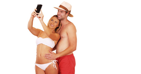 Millennial couple taking selfies with smartphone on white background