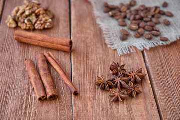 Cinnamon sticks, anise, coffee beans and nuts on a wooden background