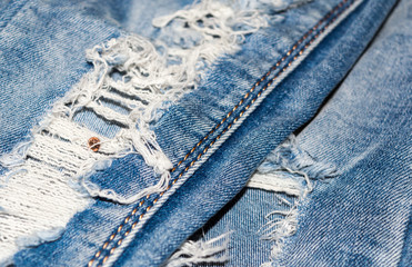 The hole in the jeans. Denim texture.