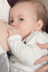 Nine months old baby girl during breastfeeding, helping herself