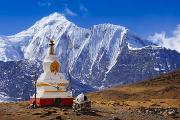 Buddhist stupa at Annapurna Circuit Trek with white summit view, Himalaya mountains, Nepal, Asia. For horizontal postcard or calendar.