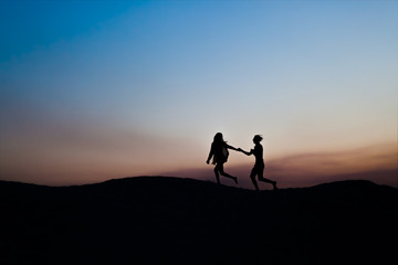 Young man and woman run together in love on a sunset. Silhouette