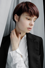portrait of a beautiful young girl with short hair near the window in a jacket, fashion
