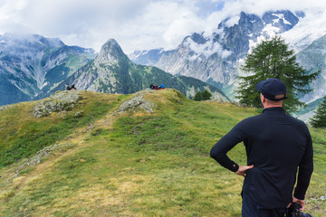 Man dressed in hiking clothing looks out over the snow covered mountains and deep forest valleys during a hike near Courmayeur, Italy