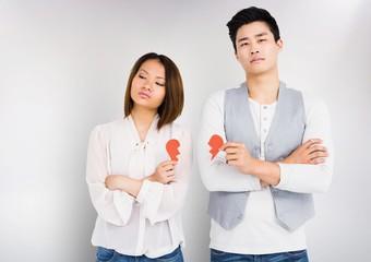 Sad couple holding broken hearts