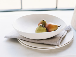 Close up of white bowl with pears in front of window