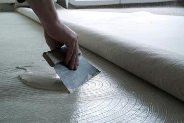 Fußbodenleger beim Auftragen von Kleber auf den Fußboden
