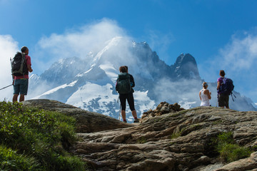 Group of hikers stand on a cliff in the French Alps above Chamonix. Tall, snow covered peaks and clouds in background.
