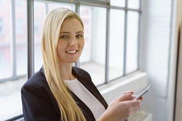 lächelnde junge frau steht am fenster und hält ihr mobiltelefon in der hand