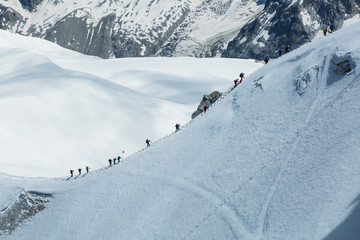 Mountaineers climb a long frozen ascent surrounded by ice and snow with a glacier in the background on Mont Blanc