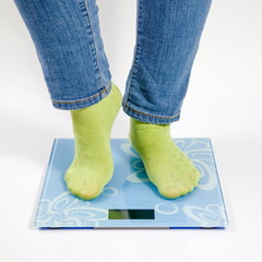 female feet in green socks standing on the blue scales