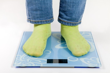 female feet in green socks standing on the scales