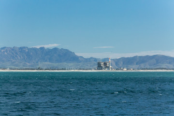 Power generating station on the coast of Ventura, California with mountains in the background