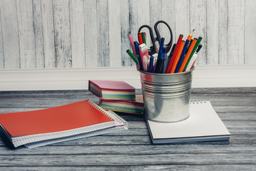 an iron pail with pens and pencils, notebooks on the table