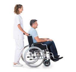 Caretaker Pushing Disabled Patient On Wheelchair